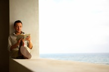 Young man reading book on window ledge